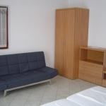 Raztegljiva zofa v sobi z zakonskim ležiščem